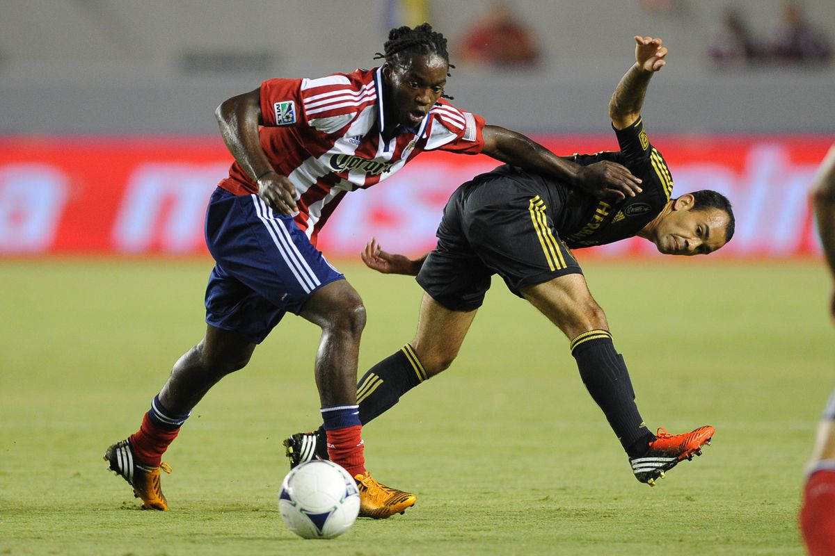 Aug 12, 2012; Carson, CA, USA; Chivas USA midfielder Shalrie Joseph (18) battles for the ball from Los Angeles Galaxy midfielder  Juninho (19) during the first half at the Home Depot Center.  Mandatory Credit: Kelvin Kuo-US PRESSWIRE