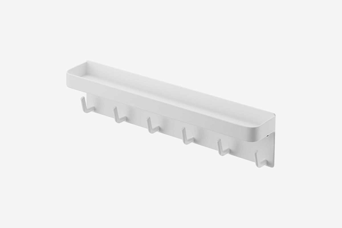 White horizontal hanger with a tray on top and hooks underneath.