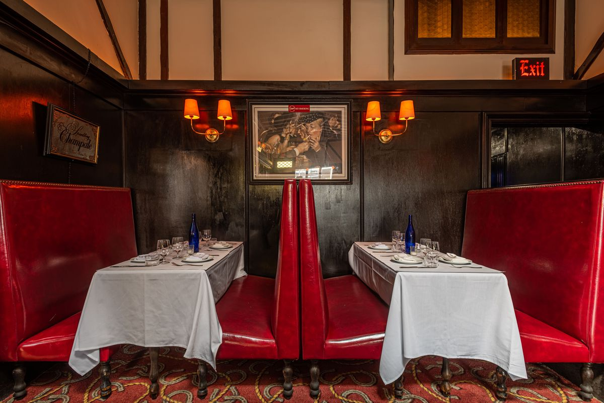 A retro look at red, tall booths and white tablecloths and wood panels in an old bar.