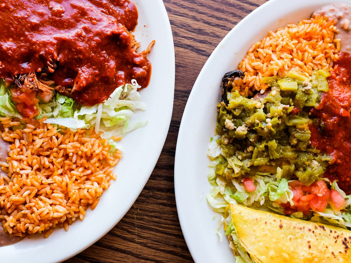 Two plates of rice, beans, tacos, stewed red pork, and lettuce on a wooden table