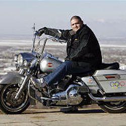 Rulon Gardner cruises through North Salt Lake on his Harley-Davidson Road King. The motorcycle features Olympic symbols.