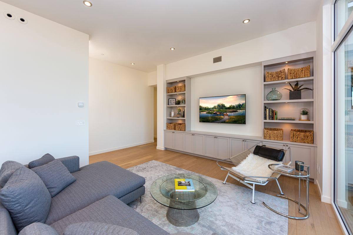 Living room with built-in shelving flanking a mounted TV.