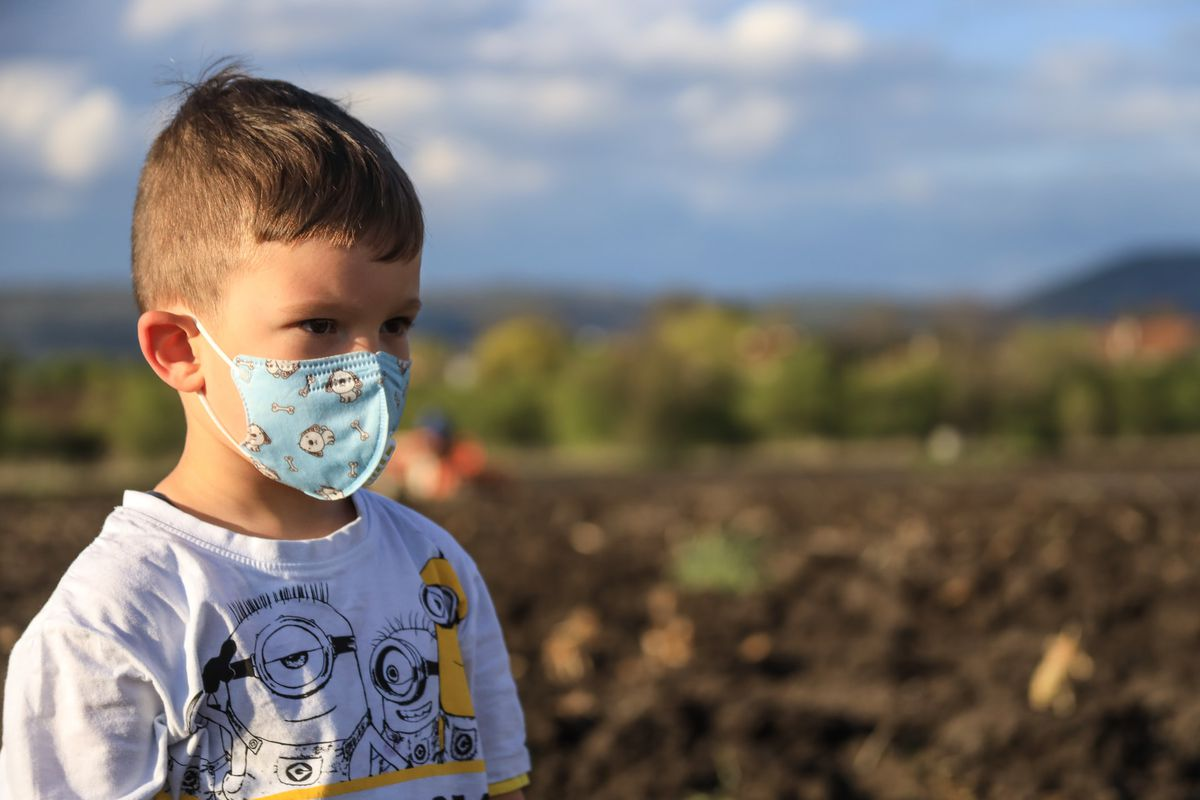 Young boy wearing a protective fabric face mask.