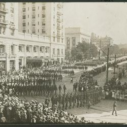 An undated photo depicts a large crowd and a parade of soldiers marching down South Temple Street turning south in front of the Hotel Utah. The photo is believed to be during the era of World War I.