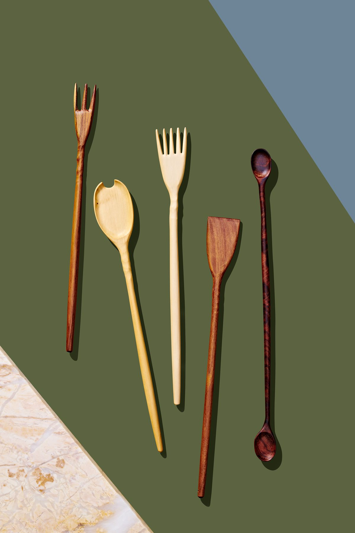 A group of five wooden utensils which are part of the 2019 Holiday Gift Guide for Curbed. The utensils which all have long handles are laying flat on a green surface with a blue accent.