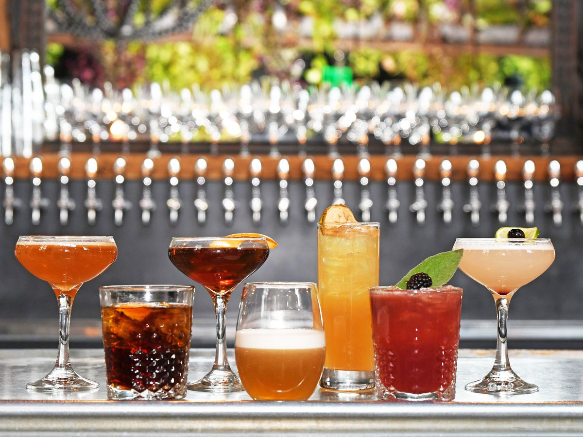 row of colorful cocktails lined up on a bar with taps in the background