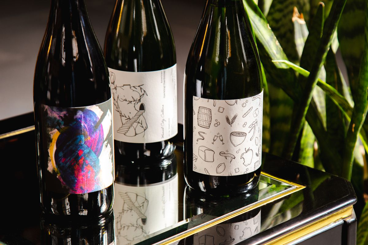 three bottles of wine with illustrations on a mirrored table