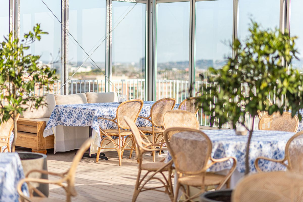 A summery rooftop restaurant setup with light blonde chairs and blue touches.