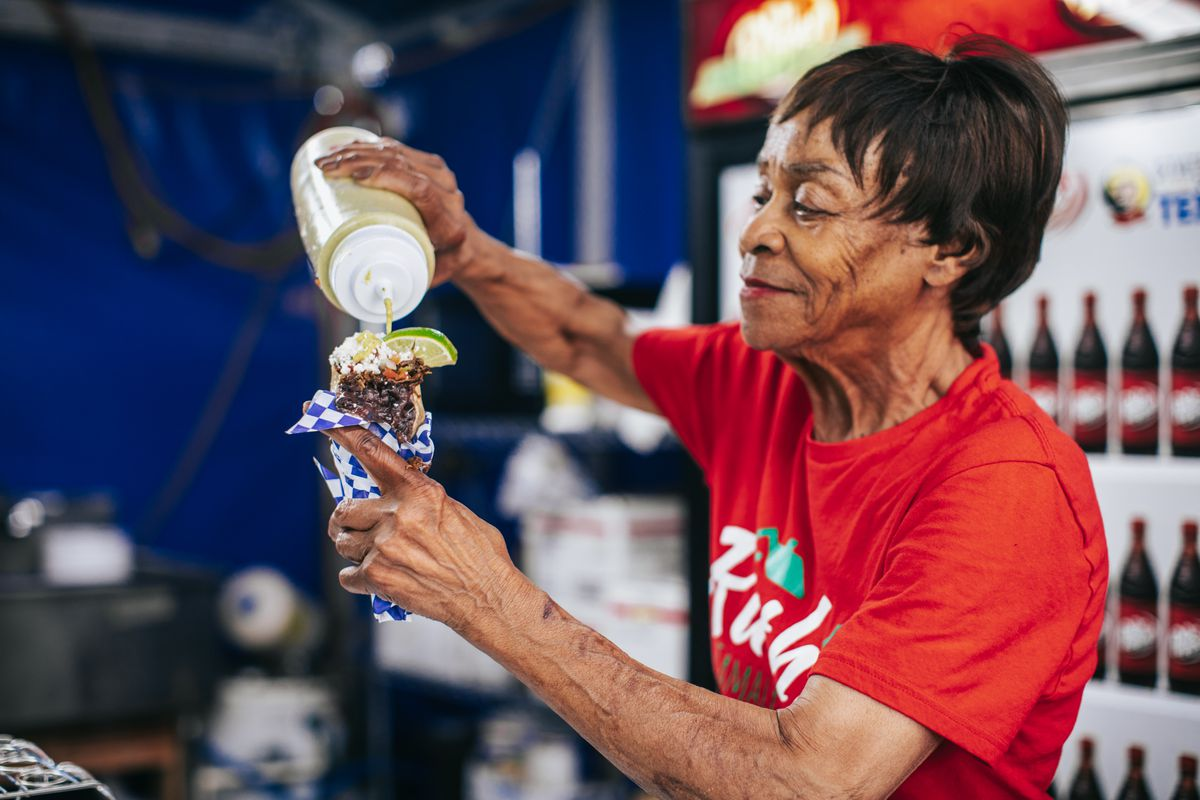 Ruth Hauntz holds a taco cone in her left hand and tops it with sauce from a squeeze bottle.