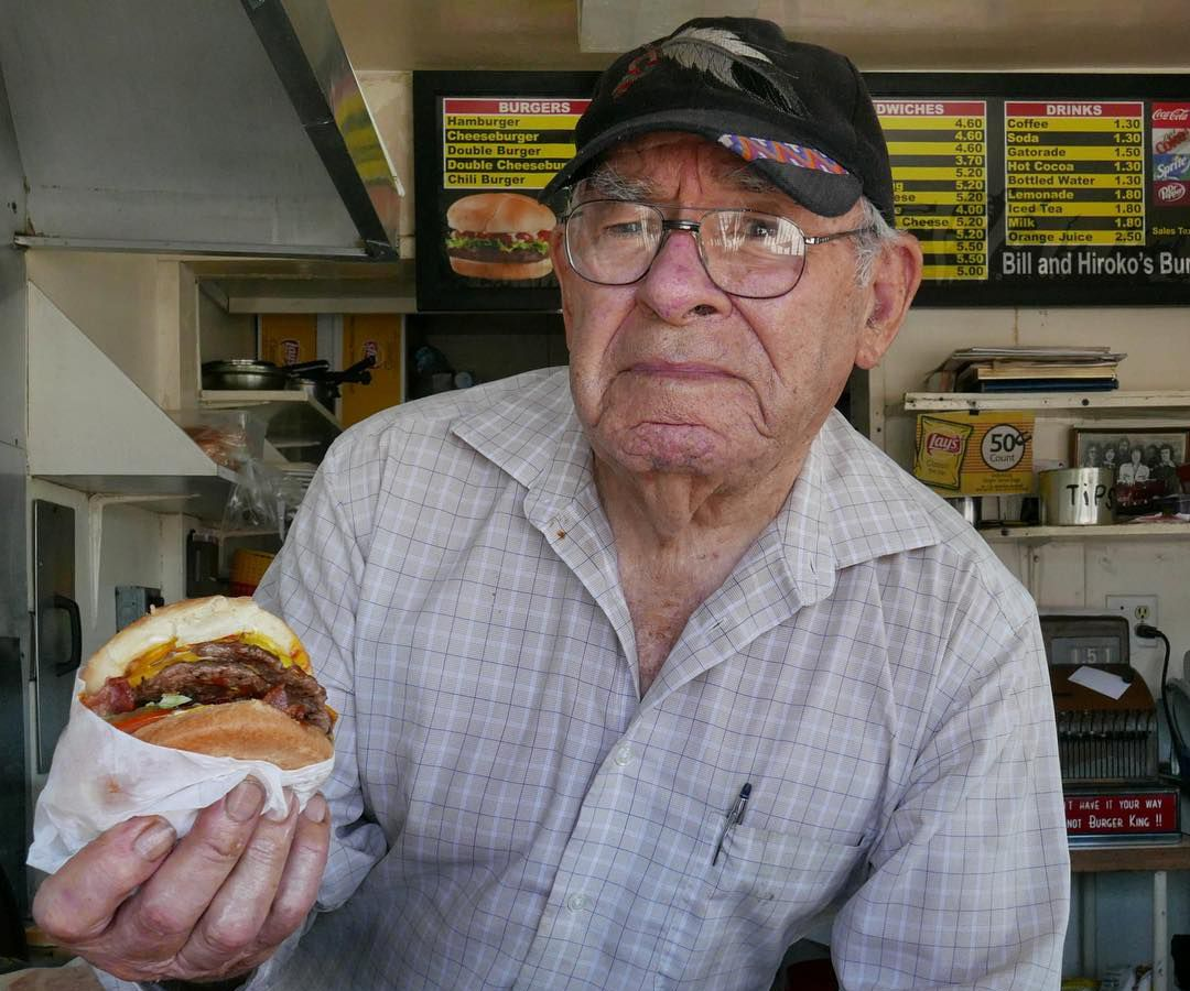 Bill's Burgers owner Bill Elwell, a 90-year-old, holds a cheeseburger as he leans into the shot.