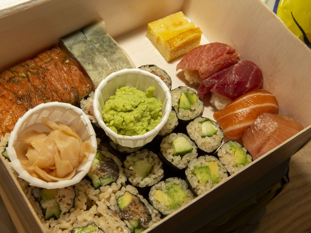 A bento box stuffed with various pieces of sushi with a ramekin of wasabi in the middle.