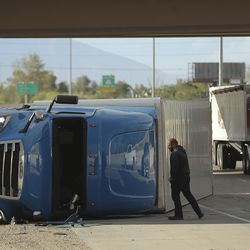 A semi is towed after rolling on I-15 after high winds toppled it in Salt Lake City on Tuesday, Sept. 8, 2020.