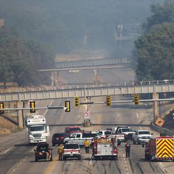 Emergency personnel are stopped on U.S. 89 near I-84 as fire burns homes and property Tuesday, Sept. 5, 2017.