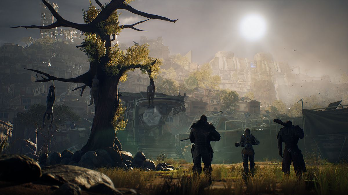 Three characters walk side-by-side past a dying tree in a screenshot from Outriders