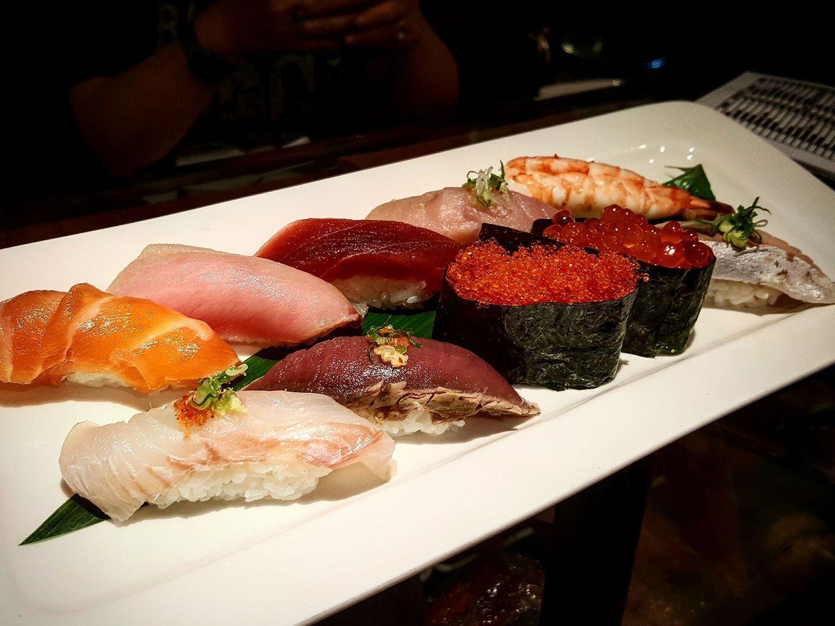 A rectangular white plate topped with about a dozen nigiri sushi