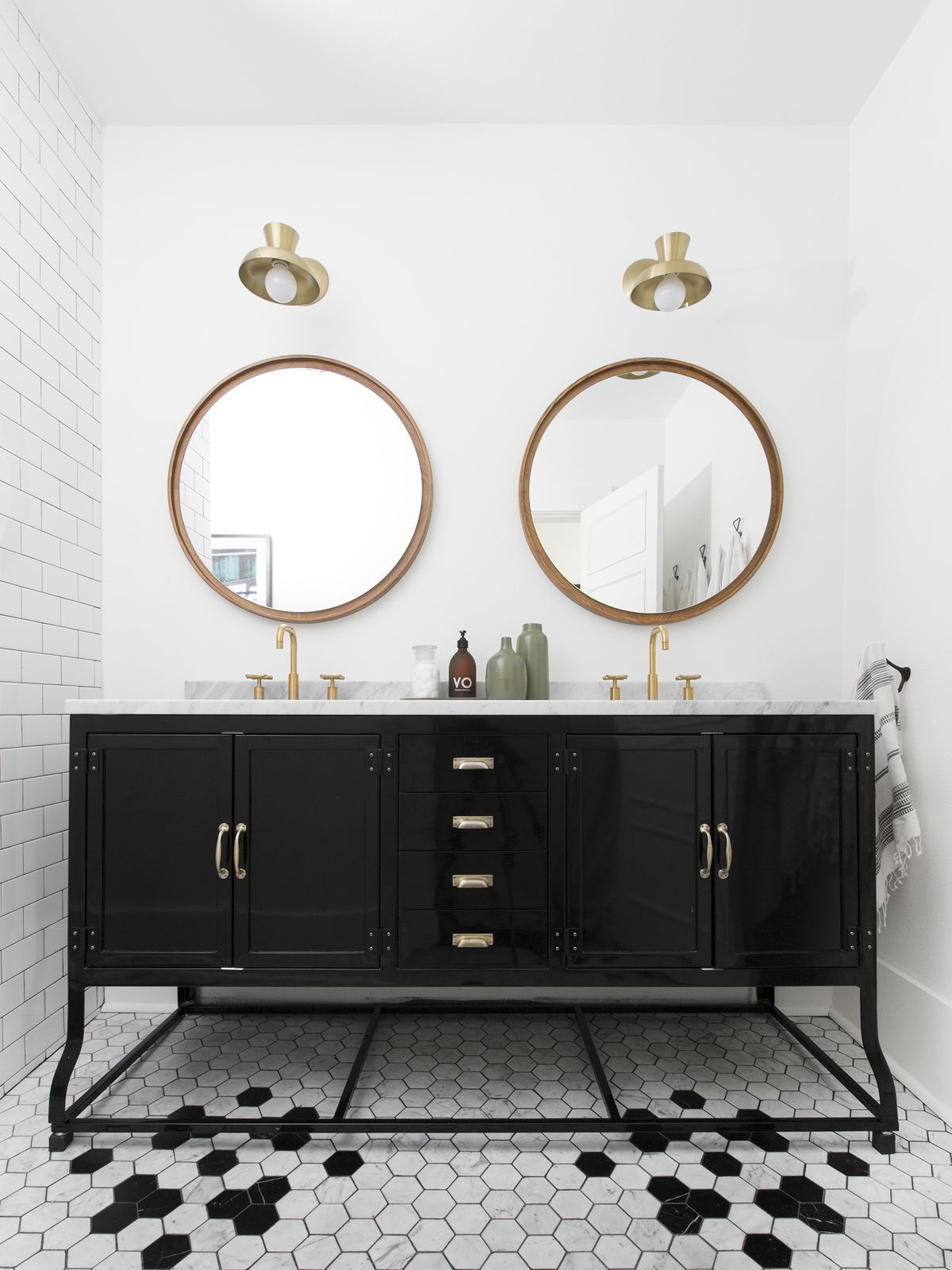 A bathroom. There is a black vanity. Above the vanity hangs two mirrors. The floor is covered in black and white tiles. The walls are painted white and one wall has white tiles. There are brass light fixtures.