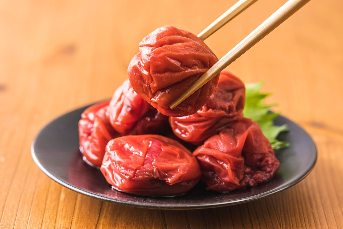 A plate comes topped with pink pickled plums, held by chopsticks