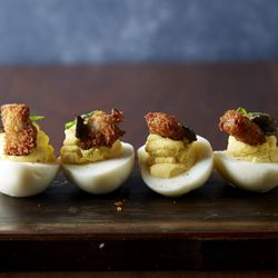 Deviled eggs are served with a chicken-fried oyster.