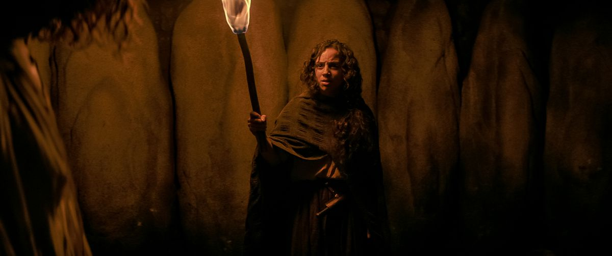 Kiana Madeira as Sarah Fier holding a torch and starring offscreen in Fear Street Part Three: 1666
