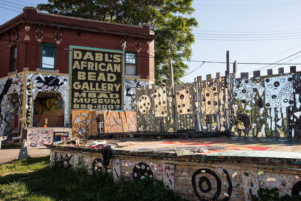 The exterior of the African Bead Museum. There is art painted on the walls and pathway. There is a sign on the museum that reads: Dabl's African Bead Gallery.