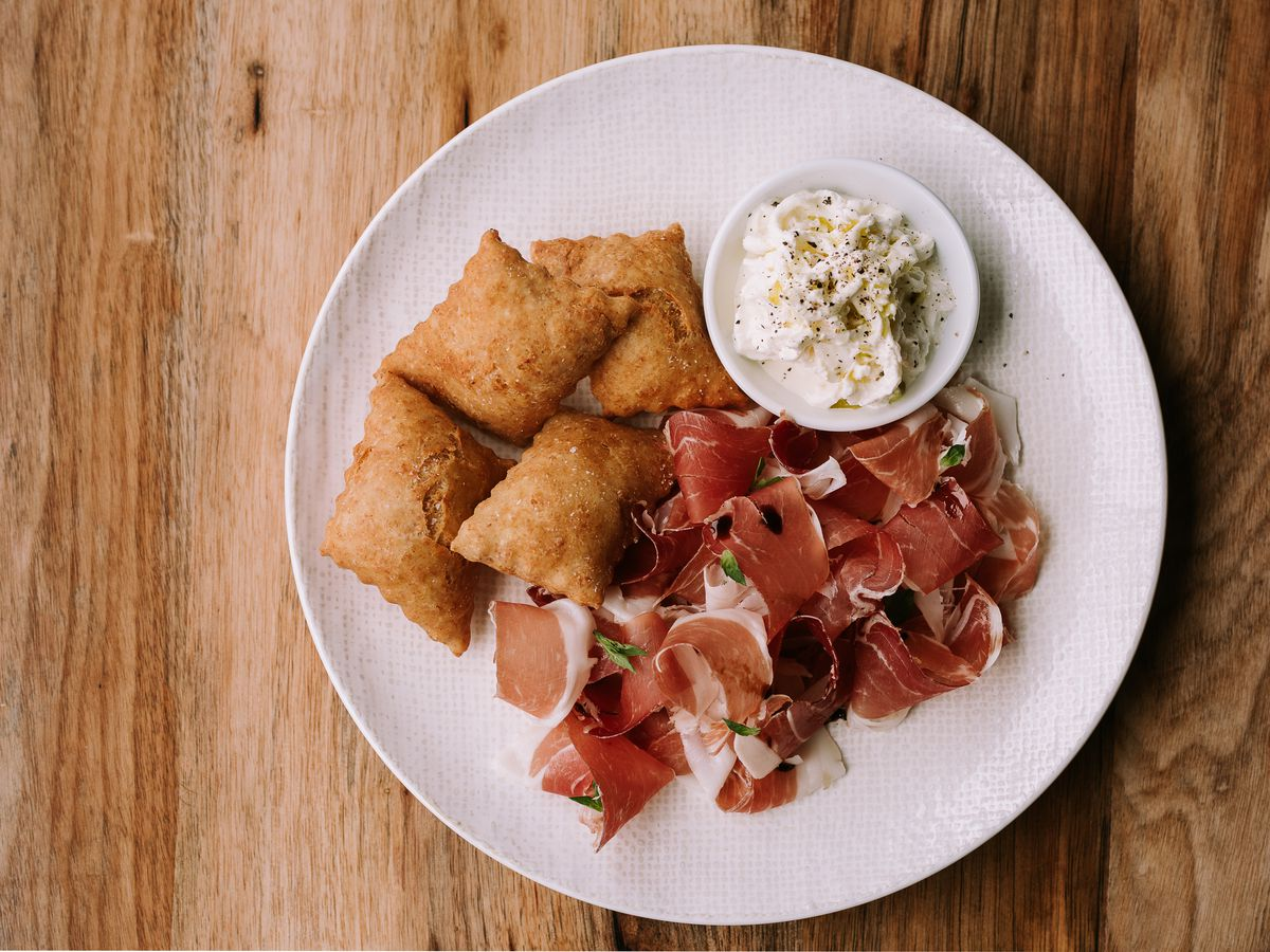 Overhead shot of a white plate on a light wood surface at Alcove in Boston's West End. On the plate is prosciutto, a small bowl of straciatella, and several bite-sized bits of fried dough.