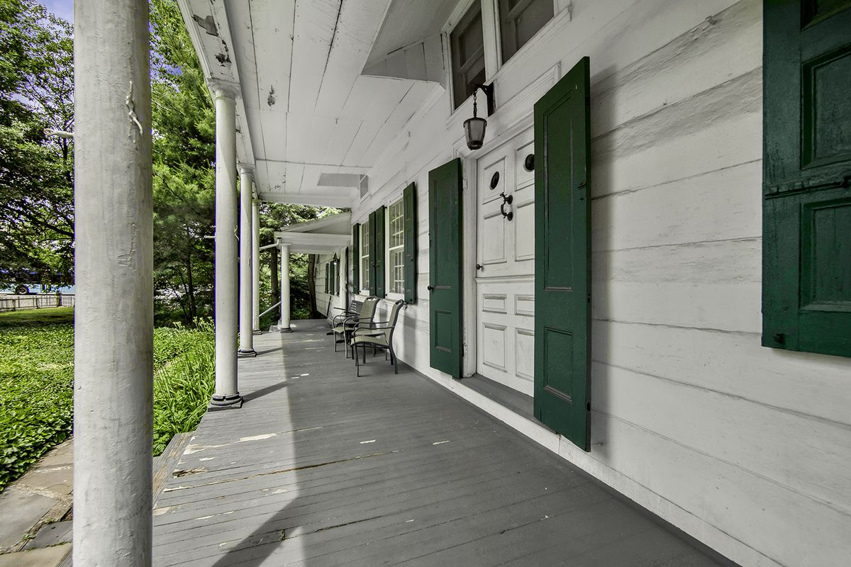 A porch with columns, wooden floors, three chairs, and a white paneled facade.
