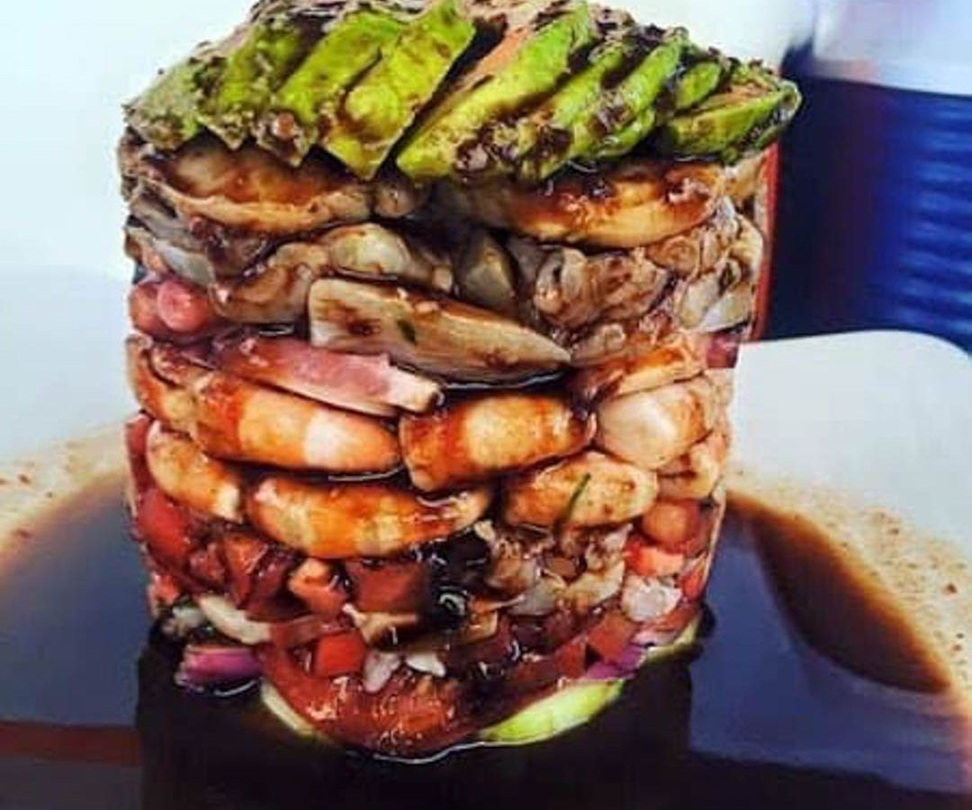 A stack of seafood with avocado on top