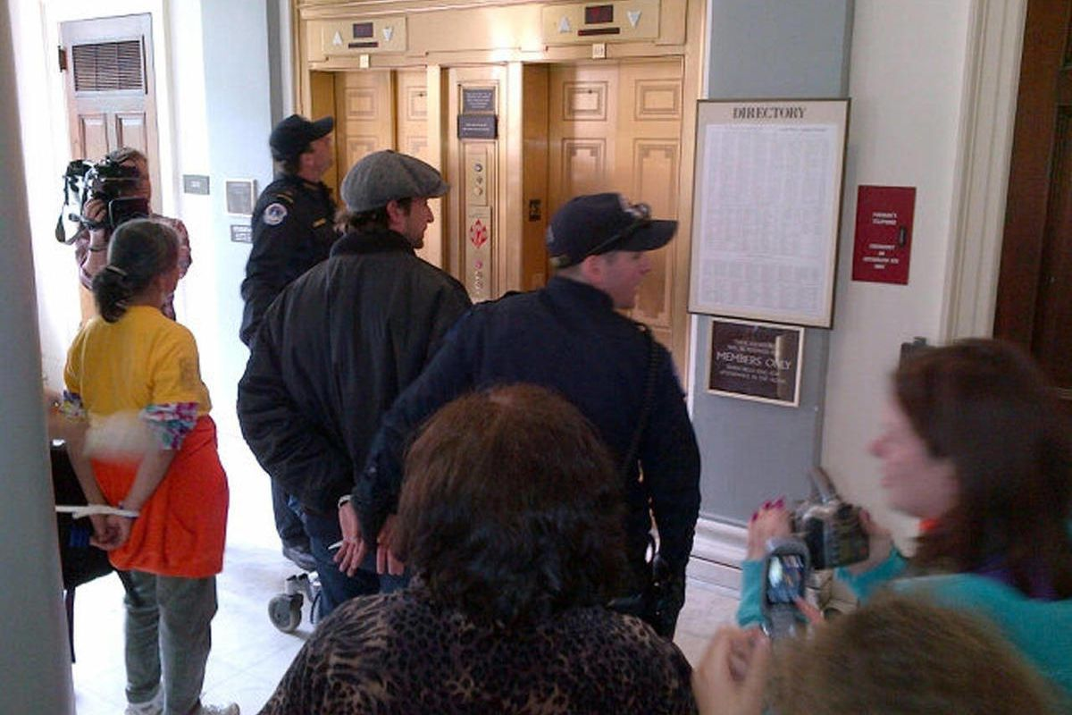 This handout photo provided by NationalADAPT shows handcuffed actor Noah Wyle, center, on Capitol Hill in Washington Monday, April 23, 2012.  Wyle and more than 100 members of the group ADAPT were arrested during a Capitol Hill protest to urge Congress no
