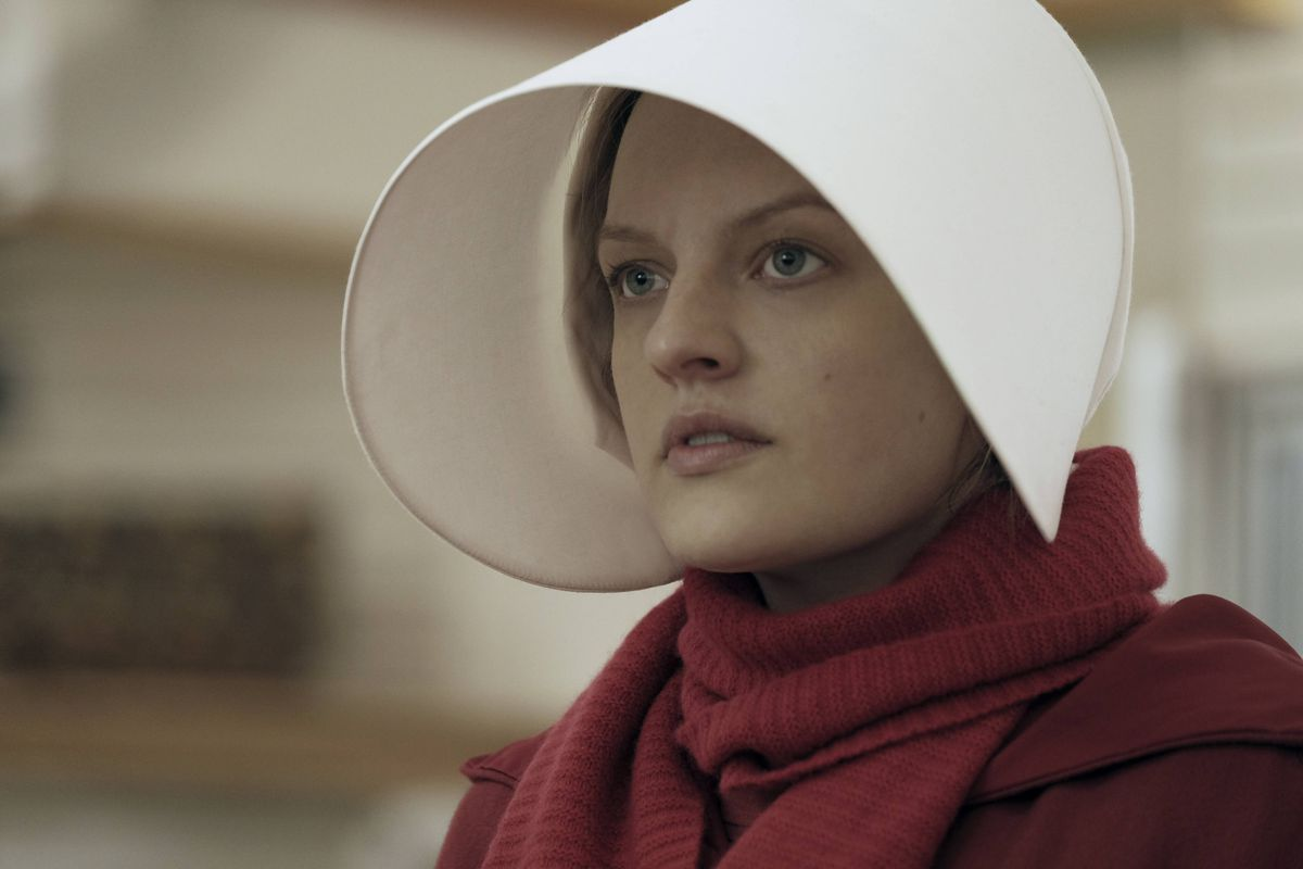 """This image released by Hulu shows Elisabeth Moss as Offred in a scene from the critically acclaimed, """"The Handmaid's Tale."""" Nominations for the 75th annual Golden Globes will be announced on Monday, Dec. 11, 2017. (George Kraychyk/Hulu via AP)"""