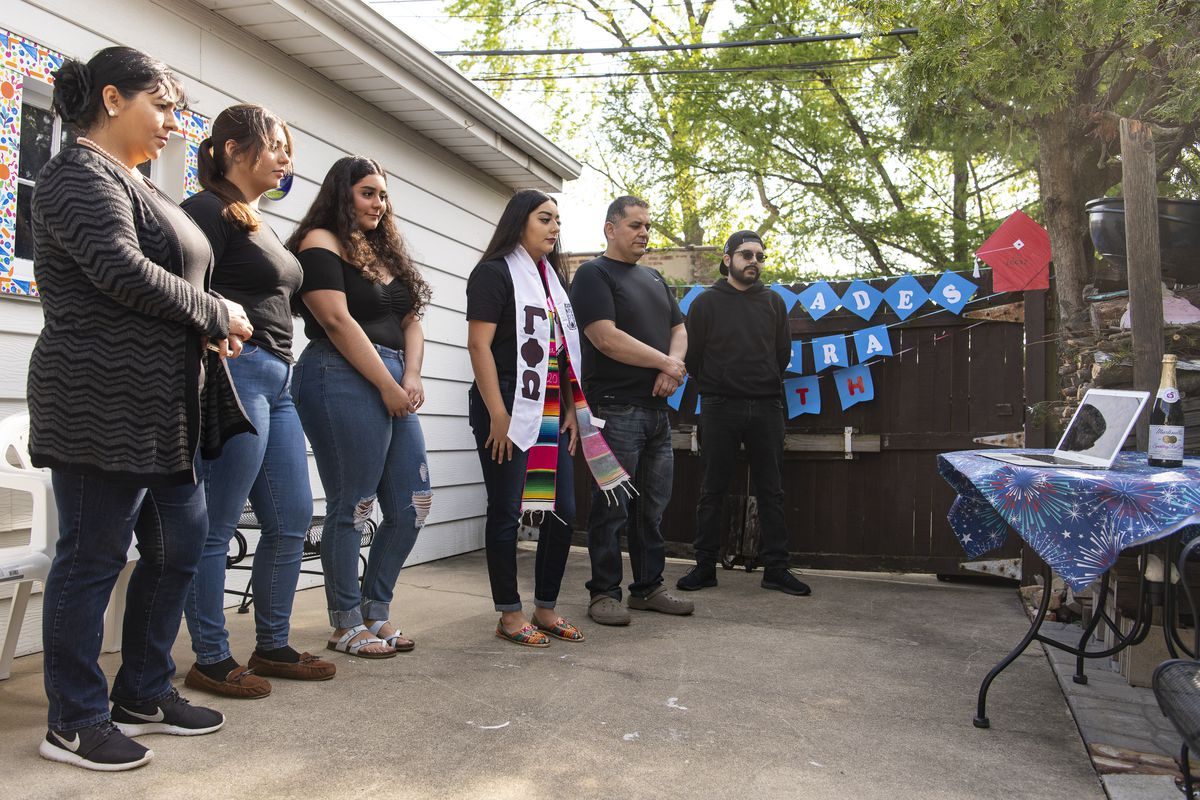 The Mendez family stands in their backyard watching UIC's prerecorded commencement ceremony Saturday.