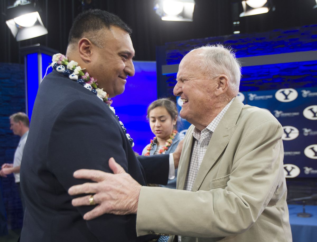 BYU's newest head football coach Kalani Sitake talks briefly with former head coach LaVell Edwards following a press conference in Provo Monday, Dec. 21, 2015.