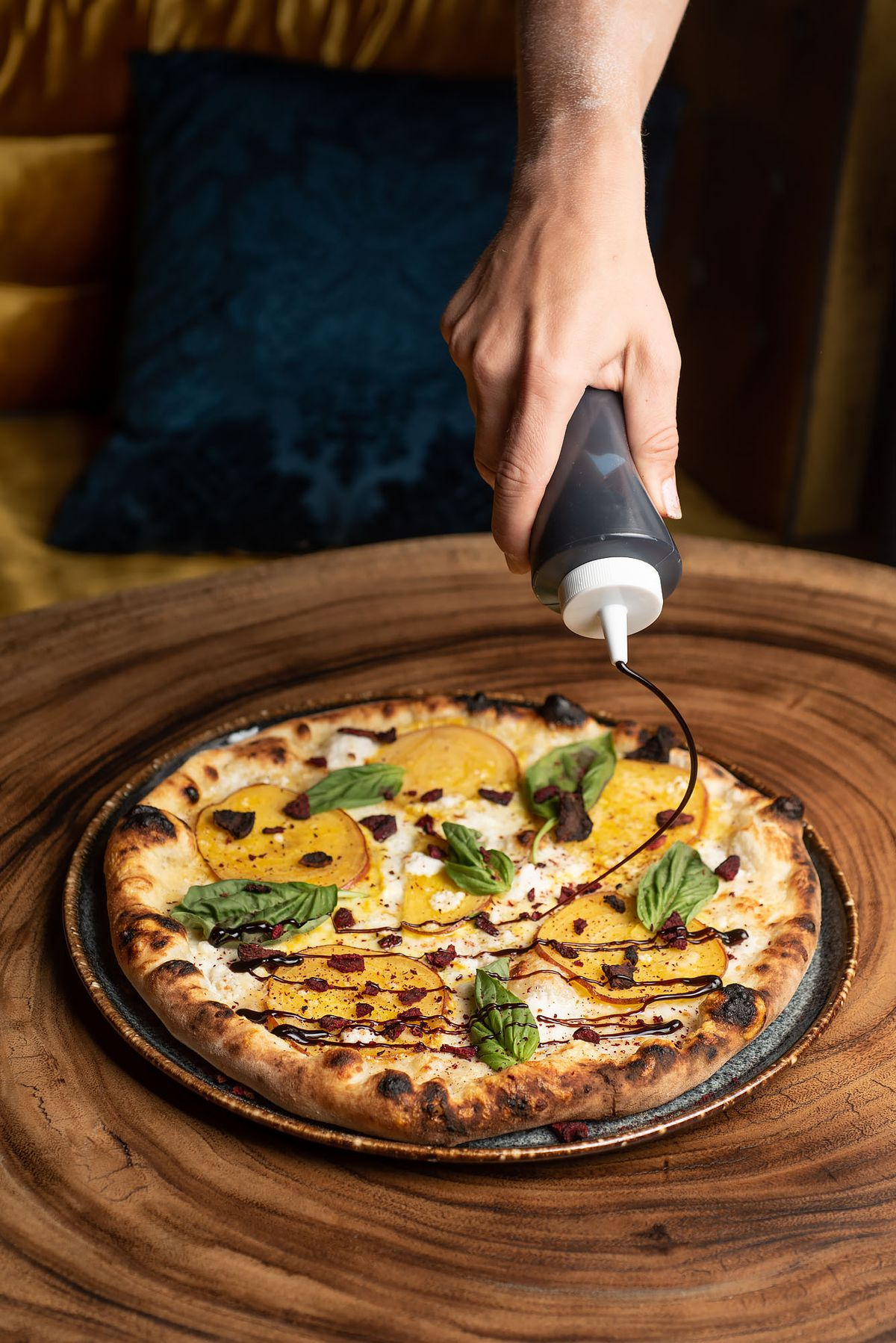 A blistered pizza topped with golden beets and drizzled with balsamic.