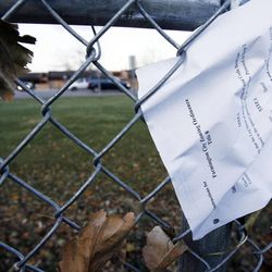 A city zoning ordinance paper is pasted by the wind to a fence near Farmington Junior High School, Thursday, Dec. 1, 2011.