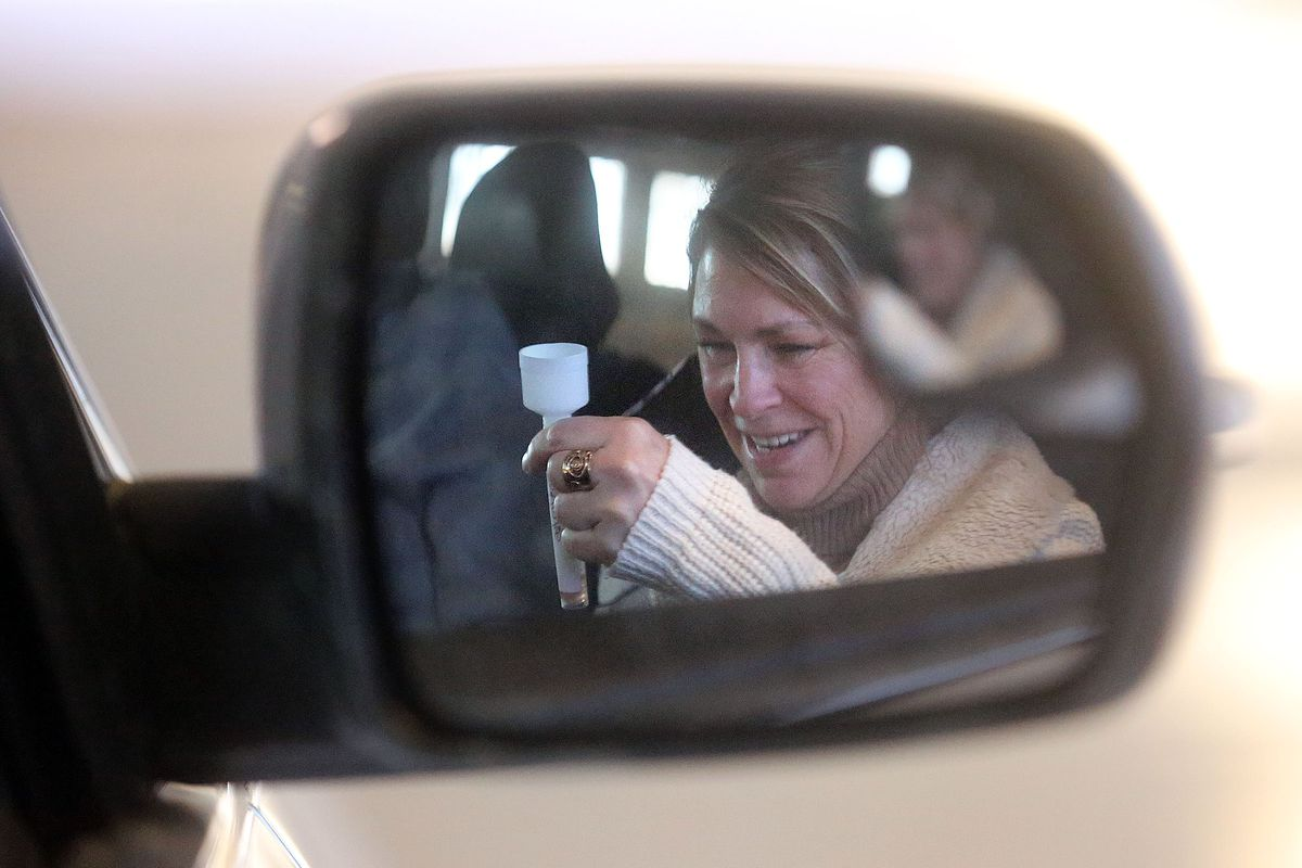 Stacey Dahlquist collects saliva for COVID-19 testing through the Wellness Bus and a University of Utah Health medical team at the Utah State Fairpark in Salt Lake City on Tuesday, Dec. 29, 2020.