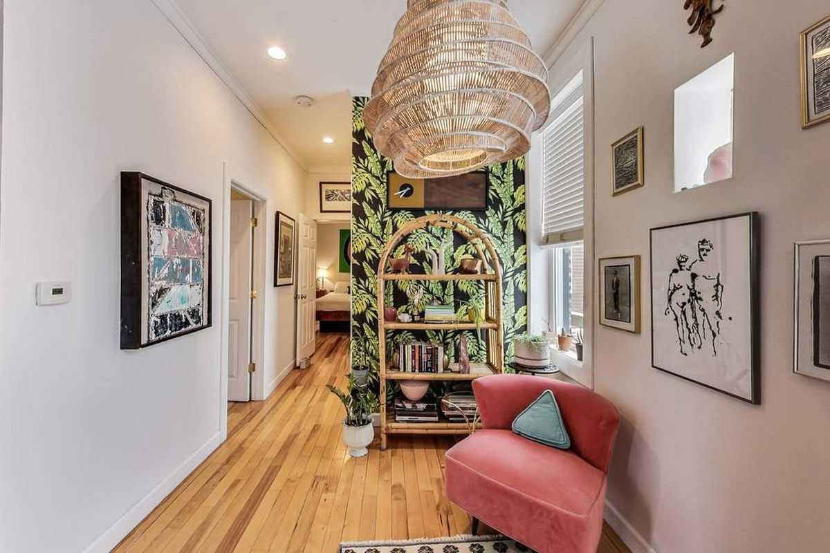 A view of the hallway with a pop of colorful leafy wallpaper, a pink chair, a woven lamp shade, and a bamboo shelf.