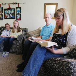 Becky Evans reads from the scriptures as she and her husband Dave enjoy family home evening Monday, May 11, 2015, together with three of their children in Murray.