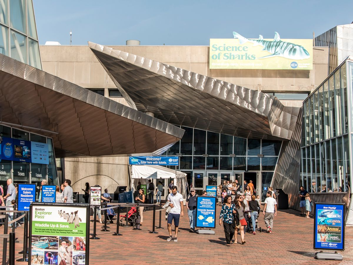 The exterior of the New England Aquarium. There are many people outside.