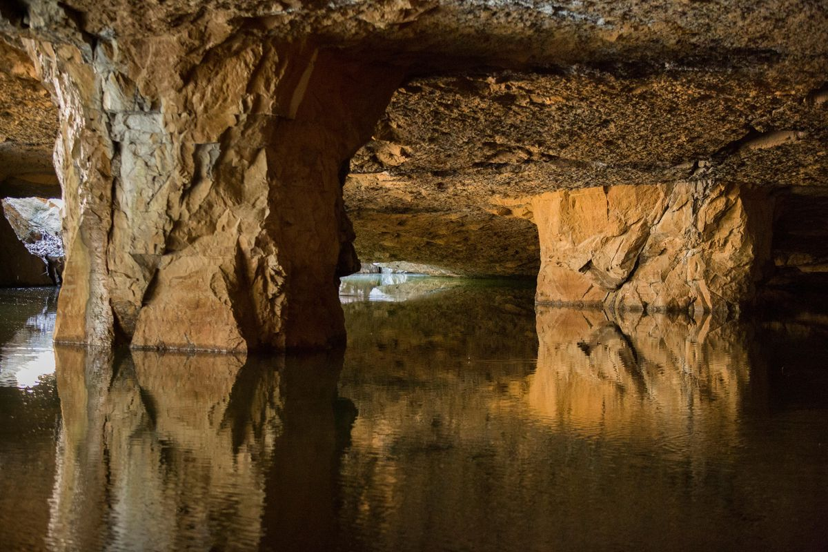 The interior of a limestone quarry. There is a body of water surrounded by rock formations.
