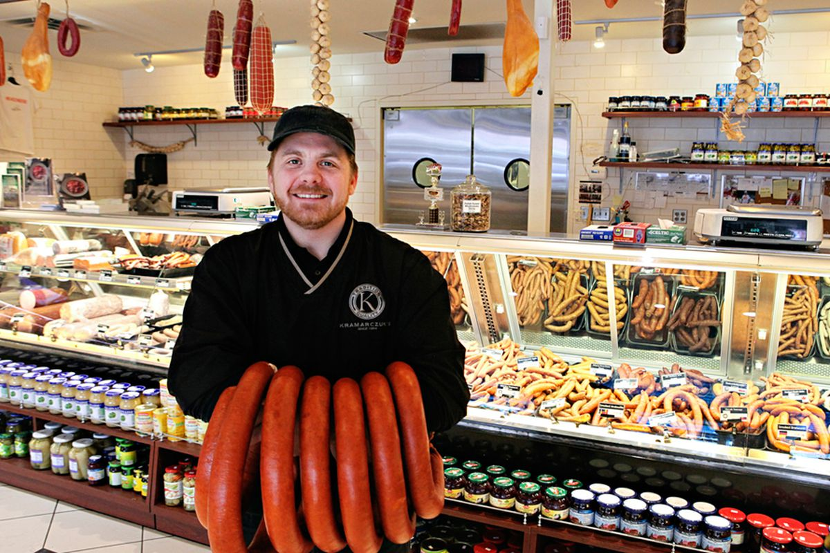 A smiling man inside the deli holds giant sausages