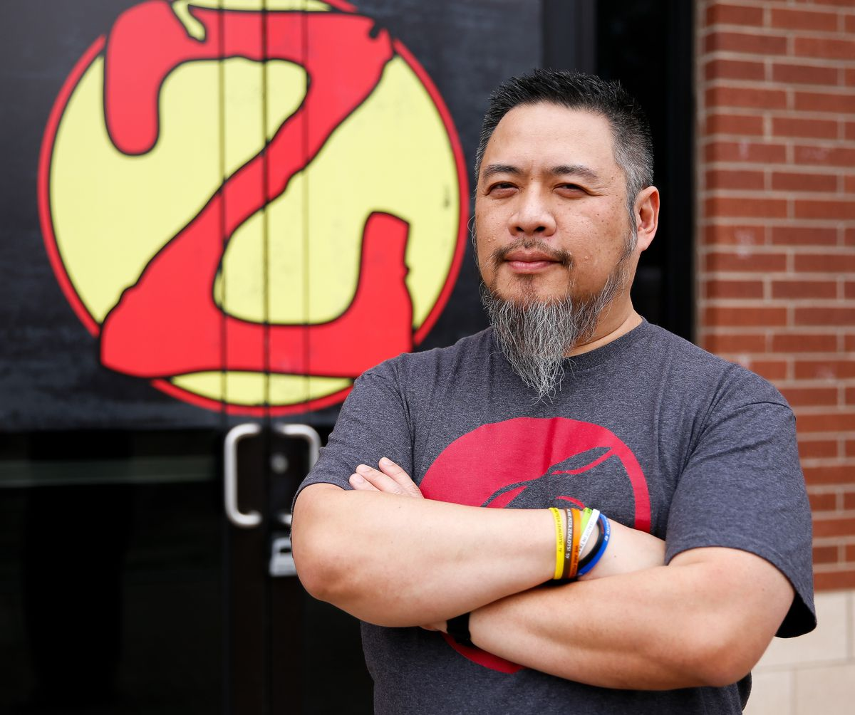 An Asian man stands with his arms crossed in front of a restaurant
