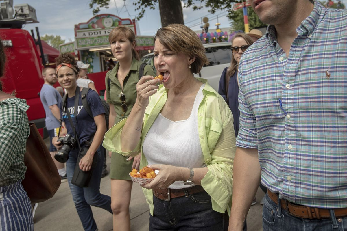 Amy Klobuchar walks while holding an order of cheese curds, and eating one with her right hand.