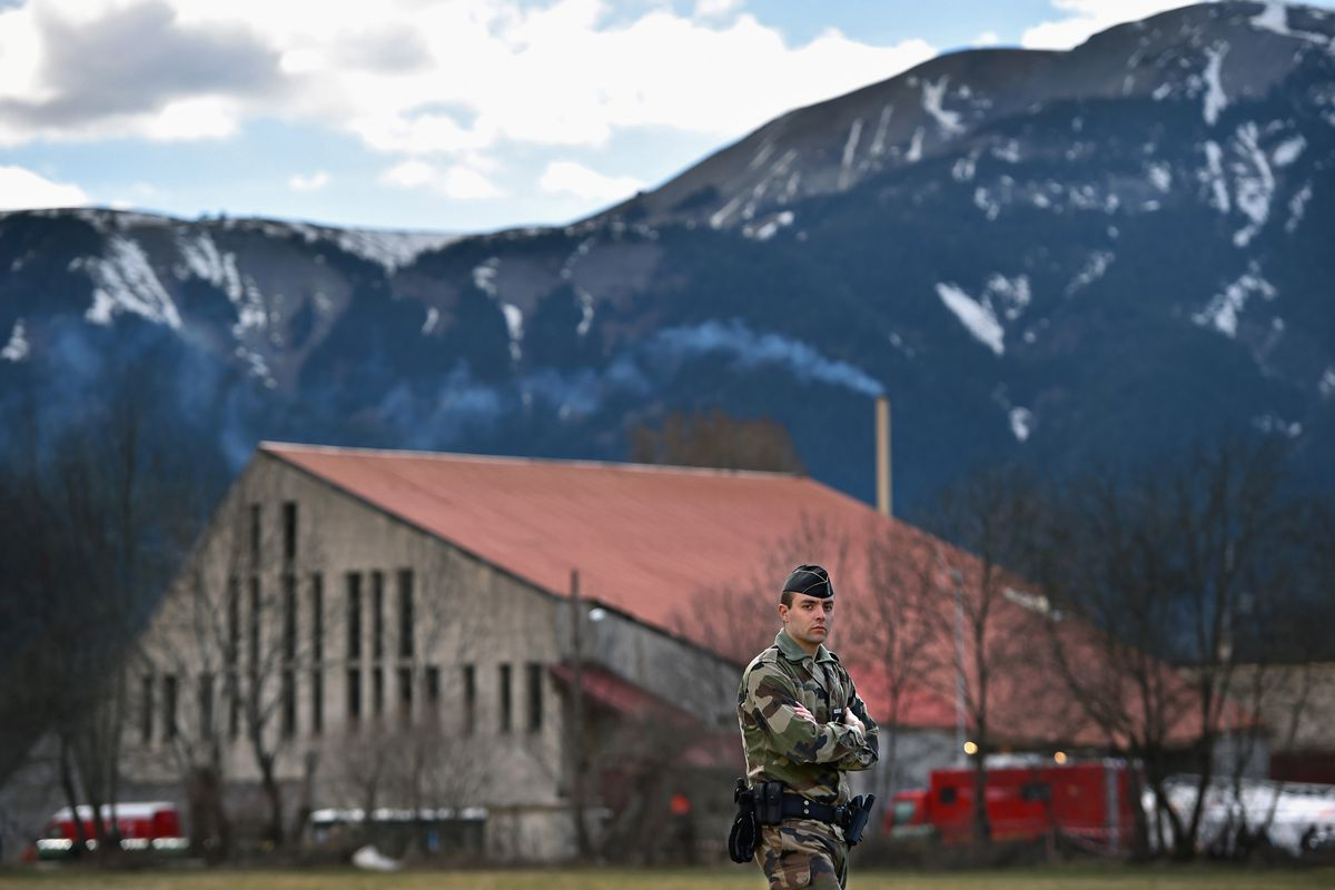 A French soldier stands guard at a gymnasium awaiting the arrival of families of the victims of flight 4U9525.