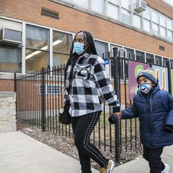 Parent Gina Lee walks with her son to drop him off at school outside of Suder elementary at 2022 W Washington Blvd in West Town, Monday, Jan. 11, 2021.