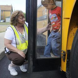 In this photo taken Aug. 18, 2012, Theresa Penkalski, left, a bus monitor in the district, helps a child off a school bus during an open house for parents and students riding the bus for the first time this school year, at the Buffalo Academy for Visual and Performing Arts, in Buffalo, N.Y. The cell phone video of a bus monitorÍs cruel taunting, in June, ignited a global outpouring of support for the monitor and revulsion at her middle-school tormentors. The video raised questions about the role of bus monitors, including how much they can really do to protect against bullies while seeing riders safely on and off the bus, and how its victim, the authority figure on the bus, could command so little respect.