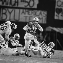 BYU HOLIDAY BOWL 1984Brigham Young University backup quarterback Blaine Fowler escapes an entanglement while trying to get a pass off during the first quarter of their Holiday Bowl game with the University of Michigan, Dec. 21, 1984 in San Diego. Fowler replaced starter Robbie Bosco who was injured in the first quarter. (AP Photo/Lenny Ignelzi)