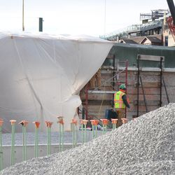 Contractors working along the right-field inner wall, behind the plastic tarp -