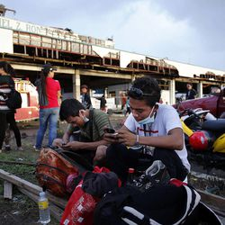 Eric Andrew Davines, front, and Richard Nube wait for a flight at the damaged airport in Tacloban, Thursday, Nov. 21, 2013. They lost their homes to the typhoon.