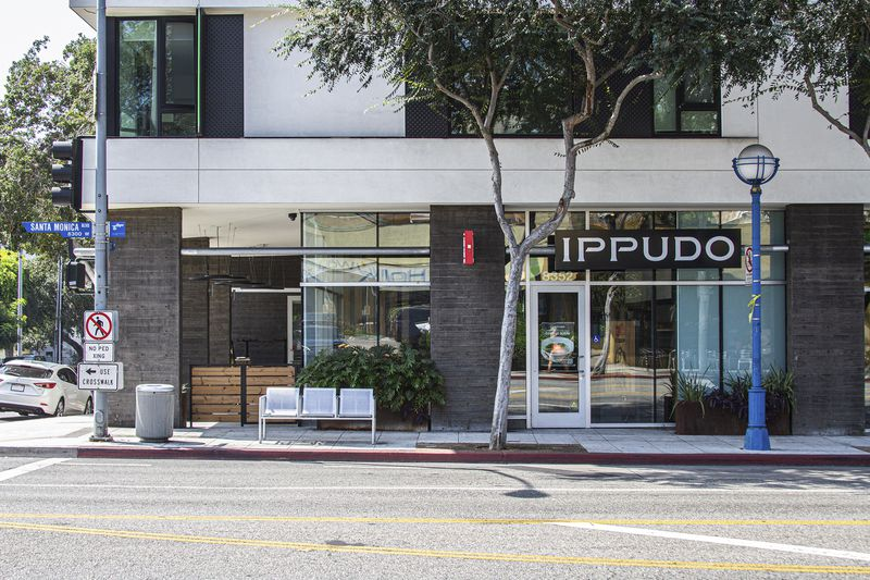 Building exterior of Ippudo ramen with street light and signage in West Hollywood.