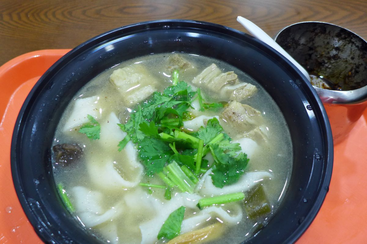 A bowl of soup with broad noodles, cilantro, and other ingredients difficult to make out through the murk.