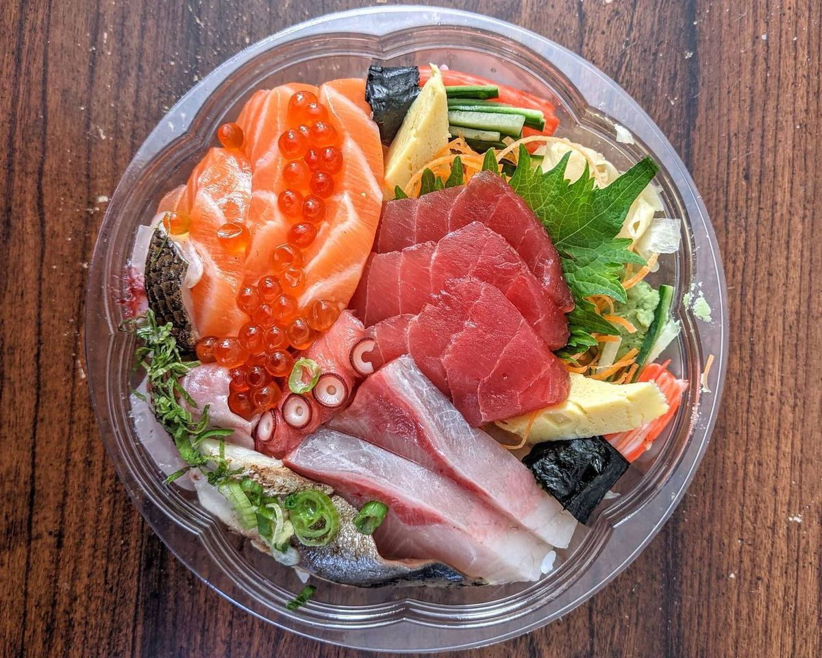 Overhead view of a plastic takeout bowl of chirashi, a variety of raw fish over white rice. There's salmon dotted with salmon roe, fat pink slices of tuna, a shiso leaf, chopped green onions, and more. The bowl is on a wooden table.